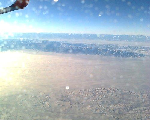 Pohoří Pamir dosahující přes 7 000 m. n. m. je z letadla jako vlnky na krajině. V takových výškách je silné elektromagnetické záření. (Foto Marie Dufková)