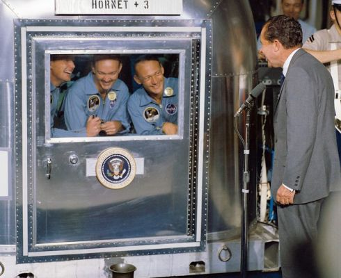 Neil Armstrong, Michael Collins a Edwin Aldrin v mobilní karanténě (MQF) na letadlové lodi USS Hornet po svém přistání do Pacifiku 24. 7. 1969, kde je navštívil president Nixon. (Zdroj NASA on the Commons)