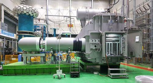 130tunový transformátor a 4metrová svorkovnice, která ho spojuje s AC/DC převodníkem, byly úspěšně vyzkoušeny v HyosungFactory v korejském Changwonu. Struktury podobné houbám vlevo vzadu patří vysokonapěťovému zkušebnímu zařízení. Tři vysokonapěťové elekt